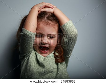 Angry Kid Girl Shouting With Open Mouth And Holding Hands The Head