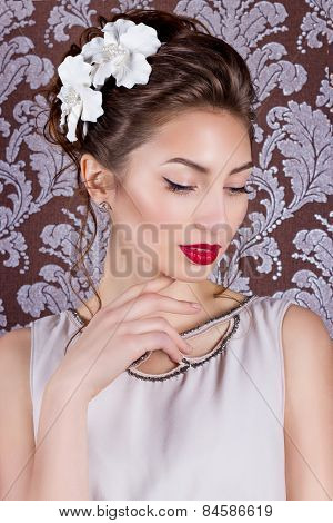 beautiful young elegant girl with bright makeup with red lips with a beautiful wedding hairstyle