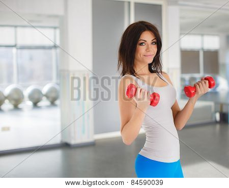 portrait of pretty young girl exercising with weight