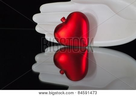 Ceramics Hand And Red Heart On The Glass Desk
