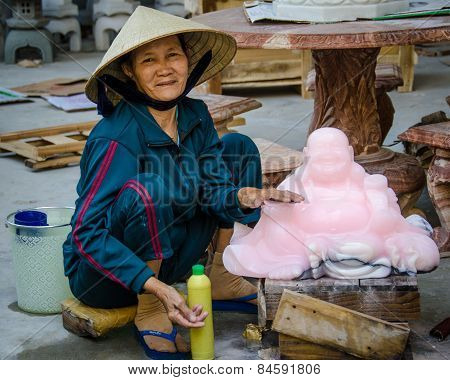 Vietnamese woman polishes marble statues of Budai,