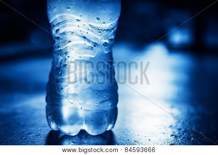 Bottle of  pure water with condensate drops and back light