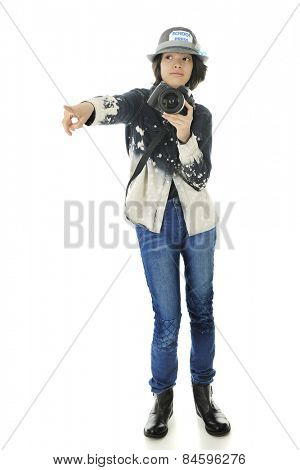 An attractive young teen school photographer with camera in hand, pointing off to her right.  On a white background.