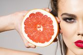 stock photo of pomelo  - Young woman holding grapefruit cut in half next to the head healthy life concept photoset of attractive girl holding a cut piece of pomelo in her hands - JPG