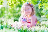 image of bunny rabbit  - Adorable little girl cute curly toddler in a colorful summer dress playing with a real rabbit having fun with her pet bunny in a beautiful garden with first spring snowdrop flowers - JPG