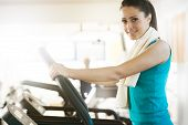 image of treadmill  - Attractive young woman smiling and doing cardio exercise on treadmill at gym.