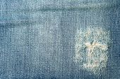 foto of ripped  - Ripped blue jeans closeup texture and background - JPG