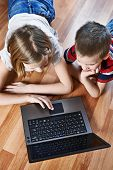 foto of fanny  - Children with laptop lying on the floor - JPG