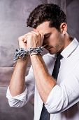 stock photo of trap  - Side view of frustrated young man in shirt and tie touching his forehead with hands trapped in chains - JPG