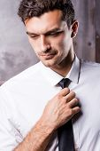 stock photo of toothless smile  - Handsome young man in formalwear adjusting his necktie and looking away - JPG