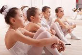 picture of ballerina  - A group of six little ballerinas sitting on the floor gathered around their teacher and listen to advice - JPG