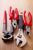 picture of claw  - Closeup adjustable wrench pliers claw hammer and pliers on the wooden background - JPG