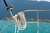 stock photo of lifeline  - A rope tied around a lifeline and a fishing rod on a yacht - JPG