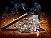 foto of cigarette lighter  - Cigar on ashtray and silver lighter on a wooden table - JPG