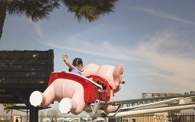 image of carnival ride  - A young girl waves goodbye as she rides an elephant ride at a carnival - JPG