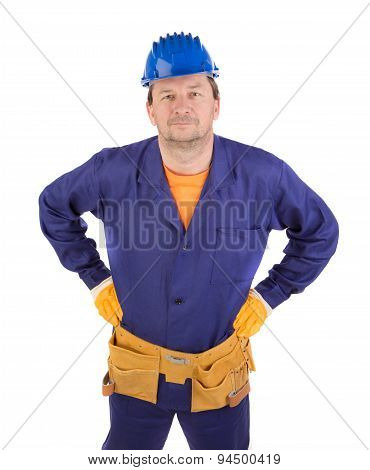 Man in working clothes with arms on waist.