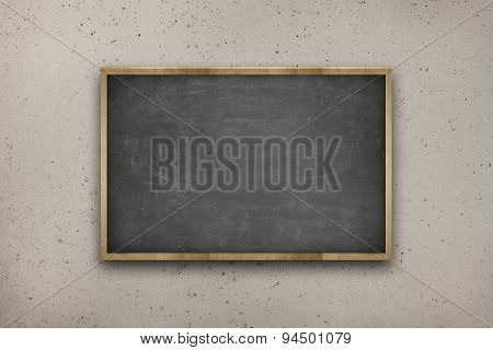 Black blank blackboard with wooden frame on concrete wall background