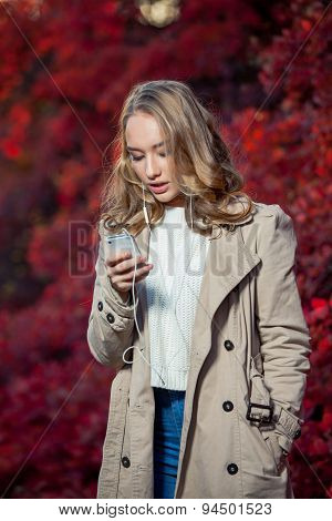 Young beauty woman writing message on cell phone in a autumn park