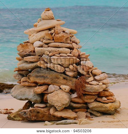 Cairn On The Pebbly Sea Beach Against The Sky