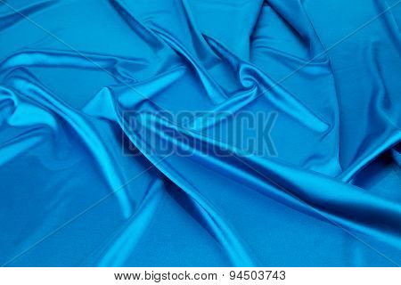 Folds of deep blue silk cloth texture.