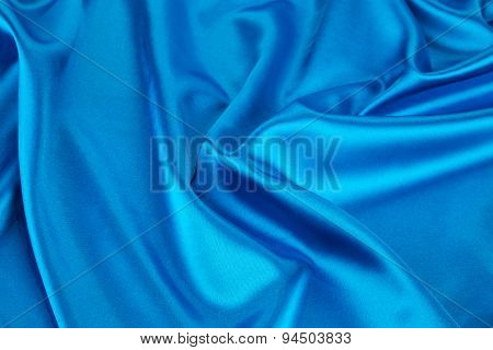 Some folds of light blue silk cloth texture.