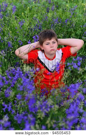 Teenage boy resting on  lawn with blue flowers