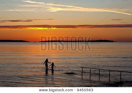 Two Girls In Sea With Sunset