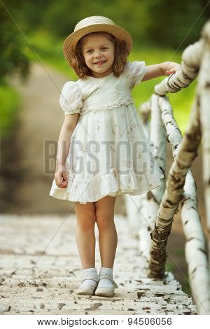 Little Girl In A Dress And Hat