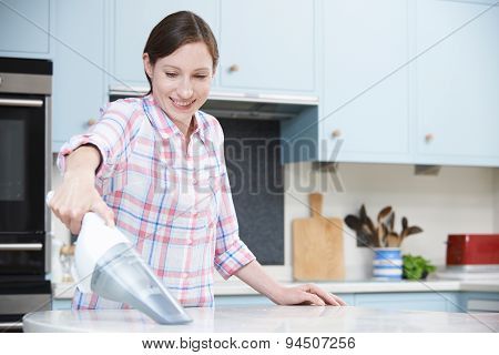 Woman Cleaning Kitchen Using Hand Held Vacuum Cleaner