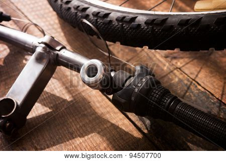 Bicycle repair. Bicycle handle bar and wheel on a wooden work bench. Intentionally shot with low key shadows. Shallow depth of field. Focus is on Shift selector of the handle bar.
