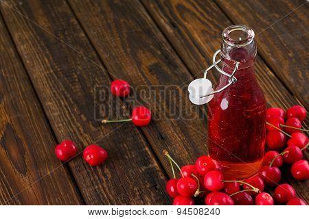 Opened Glass Bottle With Fruit Lemonade Among Several Cherries