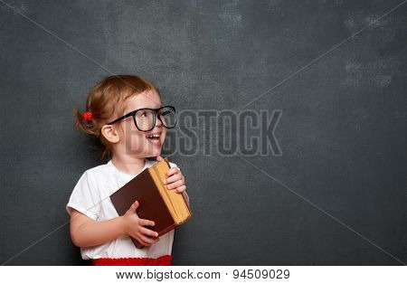 Happy  Girl Schoolgirl With Book From Blackboard