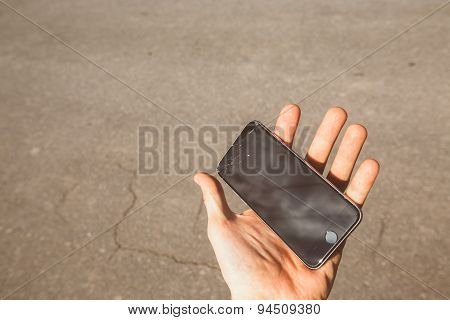 Smartphone with broken screen in hand
