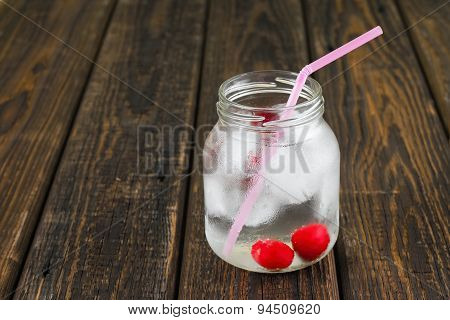 Two Cherries In Cold Drink In A Jar With Pink Straw
