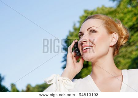 Busy woman talking per mobile phone outdoor