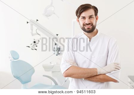 Portrait of young handsome dentist in clinic