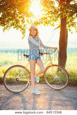 Lovely Young Woman In A Hat Riding A Bicycle Outdoors. Active People