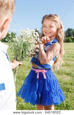 Nice little boy presenting flowers