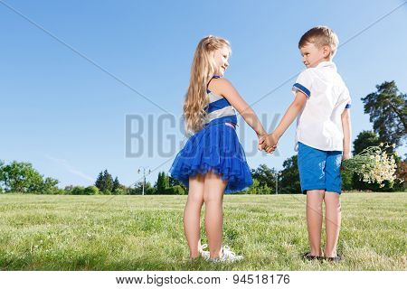 Upbeat little kids holding theur hands together