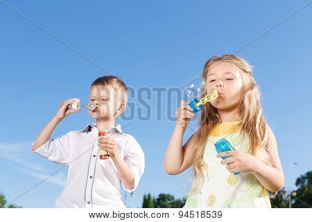 Positive children blowing soup bubbles
