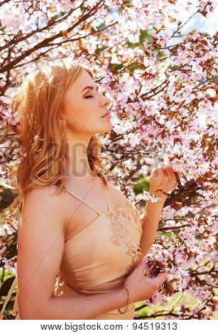 Young blond girl in spring flowers garden