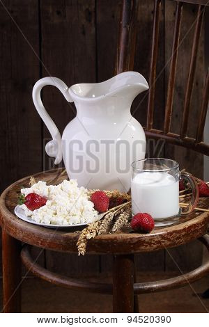 Milk In A Transparent Mug, Cottage Cheese And A Ripe Strawberry On A Wooden Table