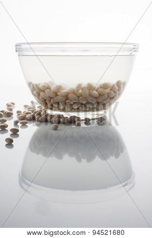 Soaked and scattered beans on white with reflection