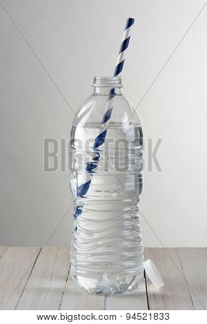 Closeup of a clear water bottle against a light to dark gray background. On a wood table the bottle has a blue and white striped drinking straw.