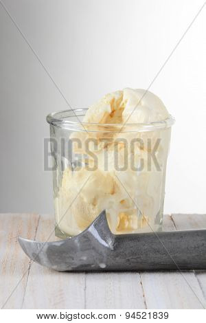 Glass of Vanilla Ice Cream and scoop on a wood table with a light to dark gray background.