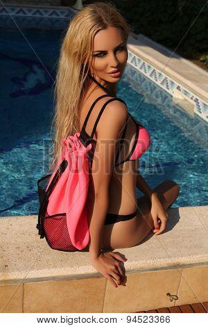 Sexy Blond Woman In Bikini Relaxing Beside A Swiming Pool
