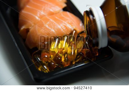 Sushi Salmon Served With Fish Oil  Pills Poured From Bottle Isolated