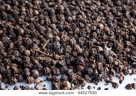 Scattered black pepper on white