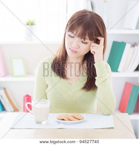 Asian woman feeling bored with her everyday breakfast, milk and cookies on dining table. Young people indoors living lifestyle at home.