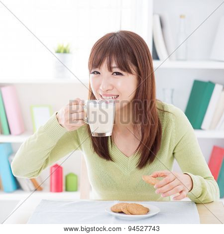 Portrait of happy Asian girl drinking soymilk and having cookies as breakfast. Young woman indoors living lifestyle at home.